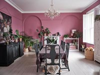 Modern dining room with pink painted walls and white floor
