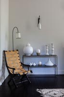White ceramics on black side table and folding chair