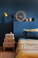 Dark blue painted walls and bedside cabinet in modern bedroom