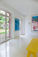Contemporary white painted corridor with yellow bench