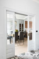 View of modern dining room through sliding double doors