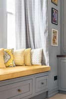 Grey built-in wooden window seat with yellow cushions