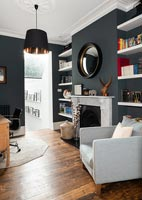 Black painted walls and white shelving in modern living room