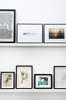 Display of black framed pictures on white shelves