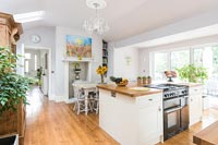 Range cooker set into island in modern kitchen-diner