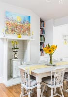 Colourful artwork above small fireplace in dining area