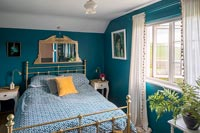 Teal painted walls in modern country bedroom with brass bed