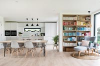 Modern kitchen-diner with bookshelves and reading chair in corner
