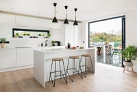 Modern kitchen with view through patio doors to barbecue area on terrace