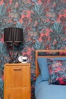 Vintage wooden bedside cabinet in modern bedroom with colourful wallpaper
