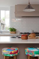 Colourful barstools in neutrally decorated modern kitchen