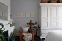 Bedroom wardrobes and chair with mantelpiece and mirror
