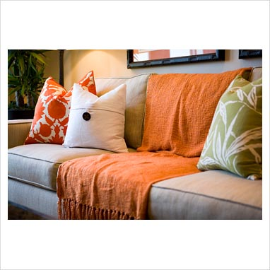 GAP Interiors  Comfortable sofa with orange throw blanket